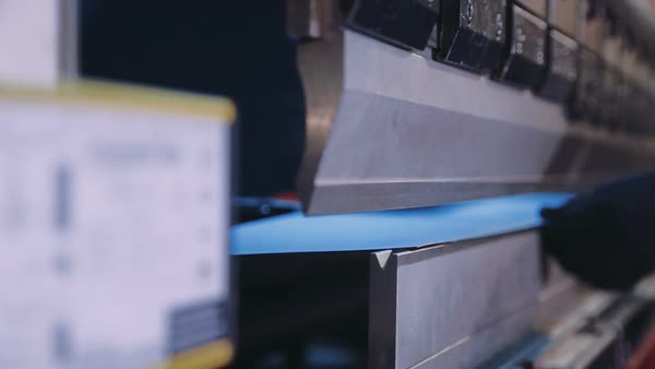 Worker is working on sheet metal bending machine stock footage