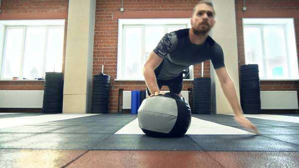Close-up of man performing uneven pushups with a ball Royalty-free stock video