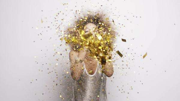 Beautiful woman blowing gold glitter confetti slow motion Royalty-free stock video