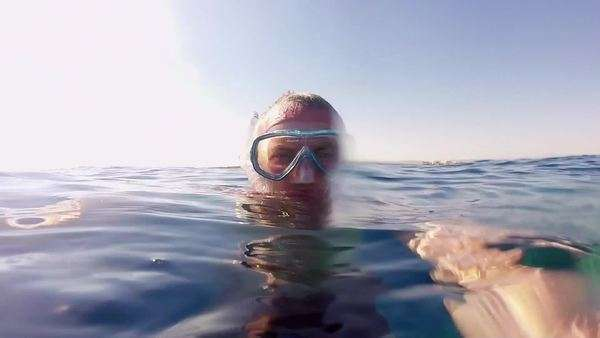 Leisure, summer fun, recreation, holiday, vacations, water sports. Man swimming underwater, apnea diving, snorkeling near coral reef, holding GoPro, Go Pro, Go-Pro video camera, Marsa Alam, Red Sea, Egypt Royalty-free stock video