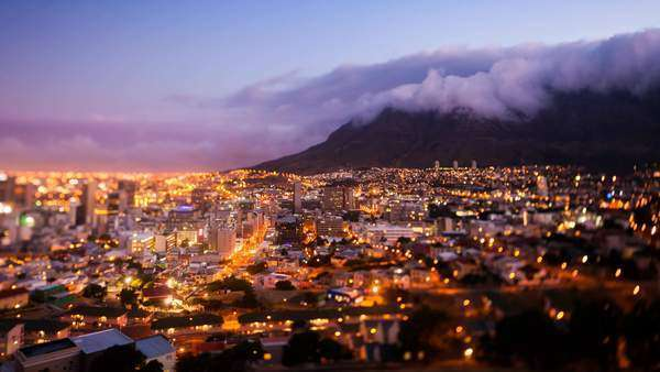 Timelapse of Cape Town and the Table Mountain during sunset and nightfall, all city lights illuminated and the signature tablecloth clouds coming over the mountain Royalty-free stock video