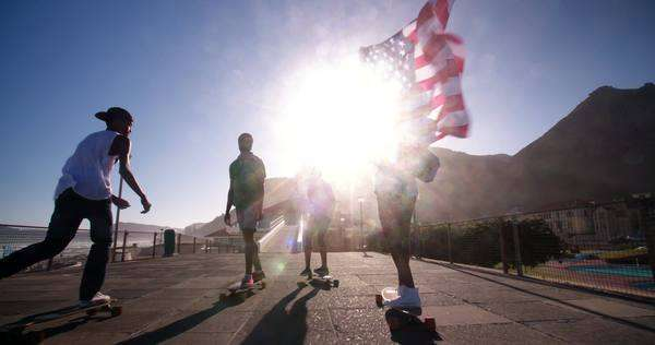 Full length shot of teenage skateboarders flying an American flag Royalty-free stock video