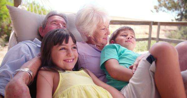 Loving grandparents spending time sitting with their grandchildren on their porch on  a summer holiday in slow motion Royalty-free stock video