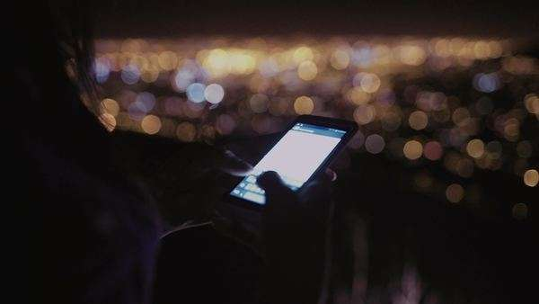 Cropped shot of a person sending an sms on a phone while standing outdoors at night Royalty-free stock video