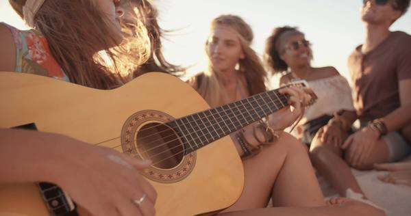 Girl playing her guitar for her friends at a beach party on a summer evening in slow motion Royalty-free stock video