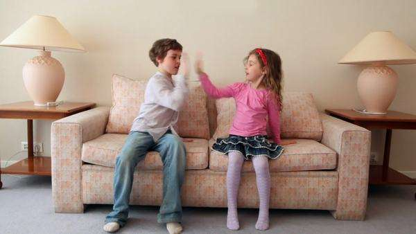 Two Kids Boy With Girl Come In Room Sit And Jump On Sofa