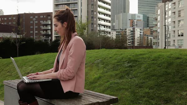 MS Woman in pink jacket sitting on bench and working on laptop/ London, England, UK Royalty-free stock video