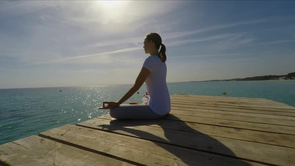Medium point-of-view shot of woman sitting on wooden pier meditating Royalty-free stock video