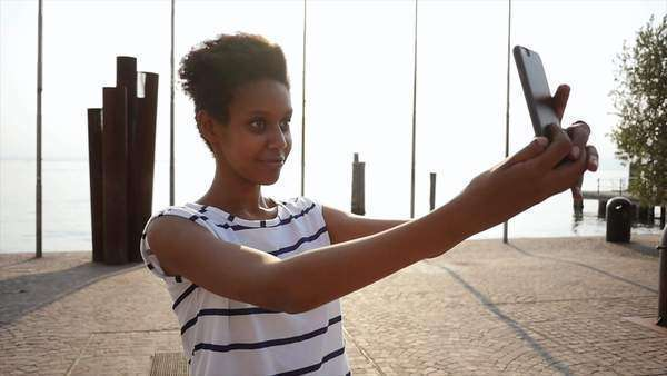 Portrait of a beautiful young woman checking the cell phone in an Italian village by the sea Royalty-free stock video