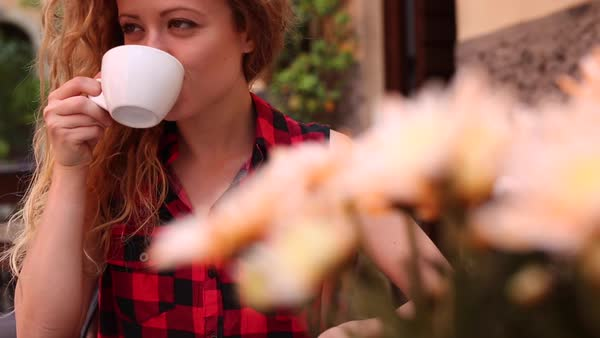 Medium close-up shot of a woman drinking a cup of coffee at an outdoor cafe Royalty-free stock video