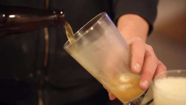 Hand-held shot of beer being poured into a frosty glass. Royalty-free stock video