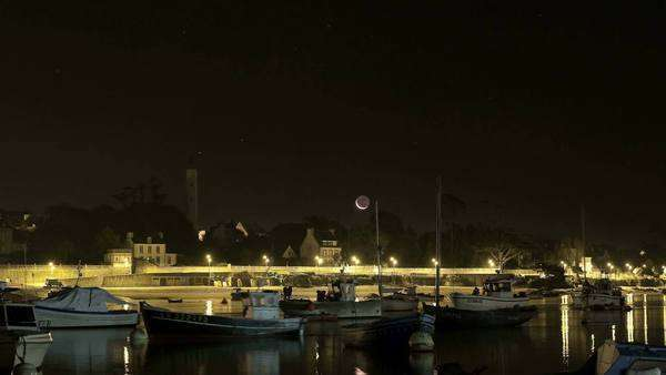 Timelapse film of Venus, Saturn and the moon in conjunction rising above Benodet lighthouse and boats in the foreground Rights-managed stock video