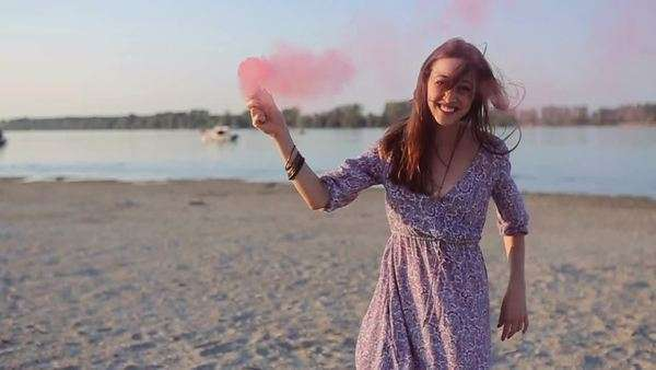 Happy Caucasian woman carrying a pink smoke bomb. Royalty-free stock video