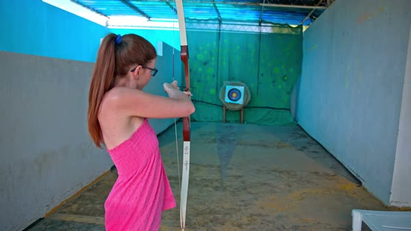 630e0d904f2de Woman in pink dress shoot an arrow in target. Behind the female person with  bow and arrow, aiming at target and release the string.