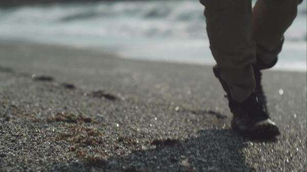 Close-up shot of man walking on sandy beach Royalty-free stock video