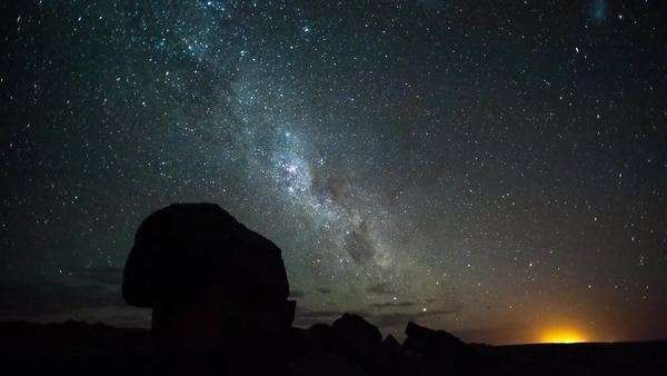 Milky Way with silhouette rocks in the foreground with scattered clouds Royalty-free stock video