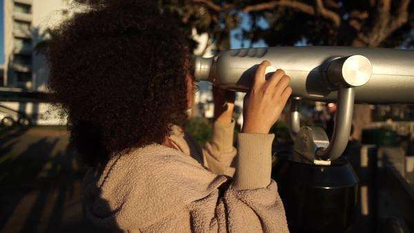 Handheld shot showing a woman using a tourist telescope Royalty-free stock video