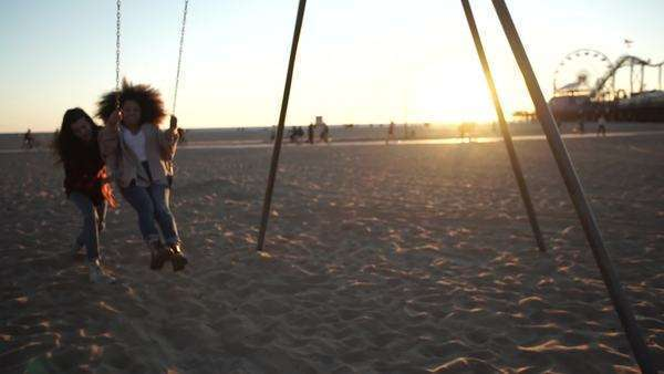 Handheld shot of a young woman jumping from a moving swing at sunset Royalty-free stock video
