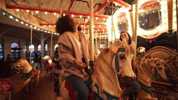 Handheld shot of a spinning carrousel capturing a happy couple enjoying the amusement ride Royalty-free stock video