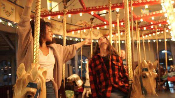 Handheld shot in a spinning carrousel showing two young people enjoying the amusement ride Royalty-free stock video