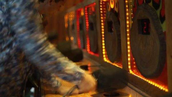Medium shot of a man playing Whac-A-Mole in an amusement park Royalty-free stock video