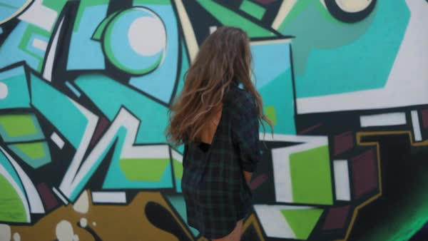 Medium shot of woman dancing in front of grafitti wall Royalty-free stock video