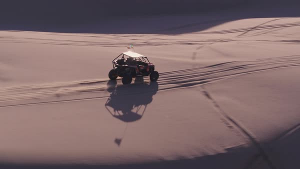 Drone shot of a dune buggy driving on the sand dunes, Moab, Utah stock  footage