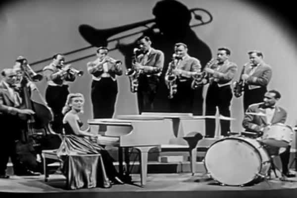 Female pianist plays a big band song with orchestra in this 1940s soundie  musical  stock footage