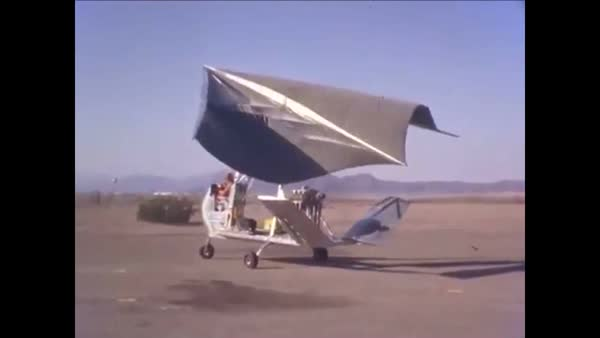 A pilot taxis on a runway near a ground crew in a Flexible Wing Aerial  Utility Vehicle at a desert airfield  stock footage