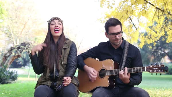 Close up of beautiful brunette woman singing and handsome man playing guitar while sitting on a tree in park Royalty-free stock video