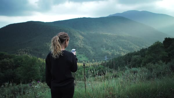 Woman looking at her cellphone alone in the mountains Royalty-free stock video