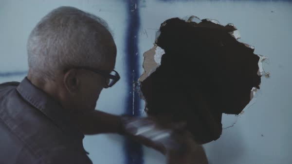 Hand-held shot of a man smashing a hole in drywall Royalty-free stock video