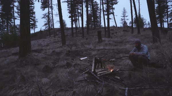 Hand-held shot of a man sitting by a campfire Royalty-free stock video