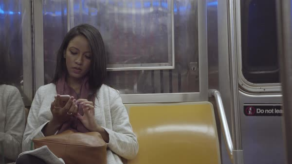 Hand-held shot of a woman using her cell phone in a subway train Royalty-free stock video