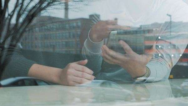 Cinematic shot through window of couple looking at iPad Royalty-free stock video