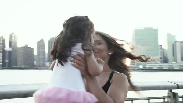 Medium shot of a mother lifting her daughter up and spinning with her Royalty-free stock video