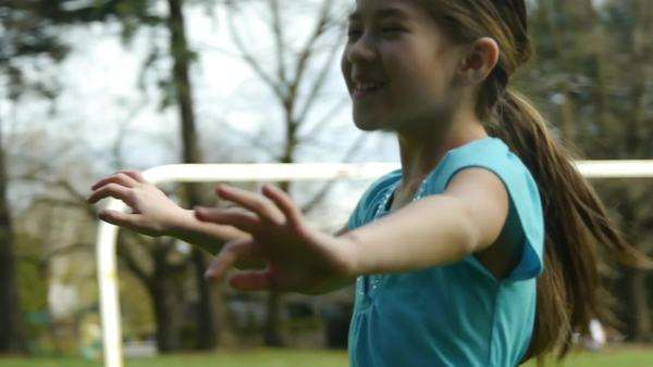 Happy girl practices using a hula hoop in the park in spring Royalty-free stock video