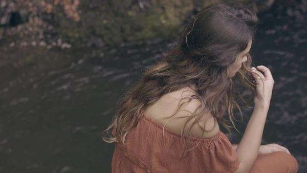 Dreamy bohemian model sits near water, plays with hair, looks around Royalty-free stock video