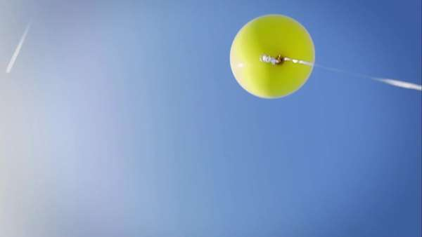A yellow balloon floats around with a blue sky in the background Royalty-free stock video
