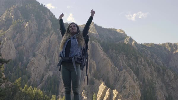 Young Woman On Solo Backpacking Adventure, Reaches Top Of Peak And Raises Her Arms In Victory, Then Gives Peace Signs Royalty-free stock video