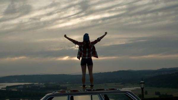 Young woman stands on her car and takes in the surrounding beauty, she raises her arms and jumps up and down in awe of the view Royalty-free stock video