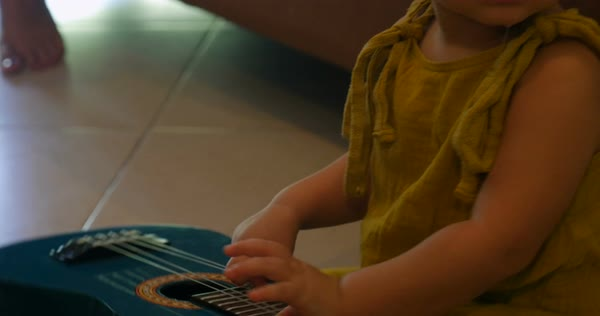 Cute baby playing with a small toy guitar while sitting on a floor stock  footage