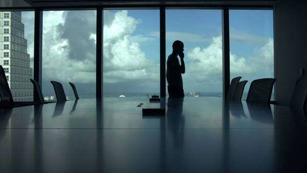 Silhouette of businessman alone in boardroom talking on mobile phone. Royalty-free stock video