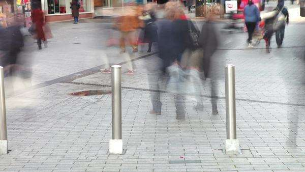 Timelapse sequence showing shoppers on busy street walking through barriers. Royalty-free stock video