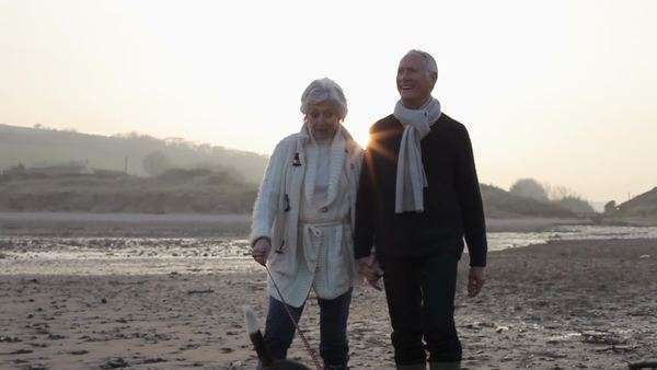 Senior couple walking along beach towards camera. Royalty-free stock video