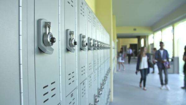 Camera Tracks Along Lockers In High School With Students Walking Along Hallway In Background Stock Video Footage Dissolve
