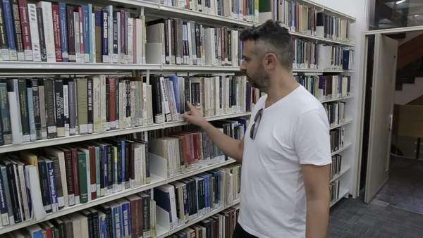 Shot of a university student in the library stock footage