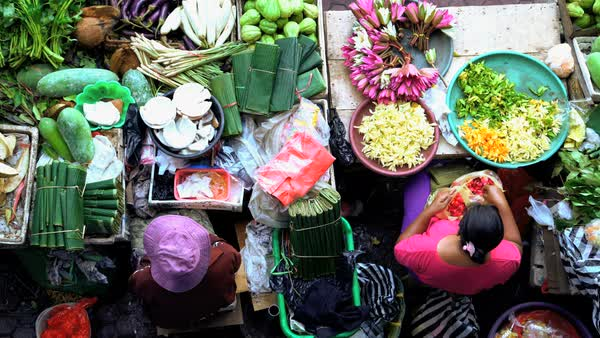 Bali, Indonesia - August 2016: Urban scene of female street market trader  selling fresh flowers and spices to Indonesian tourists and local people
