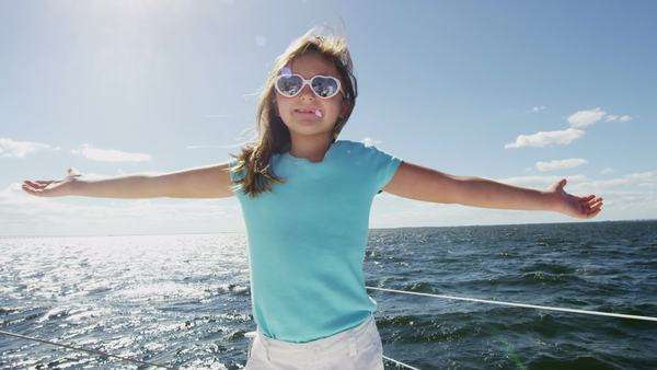 Young girl with her arms outstretched at the front of a yacht as it sails through water during sunny afternoon Royalty-free stock video