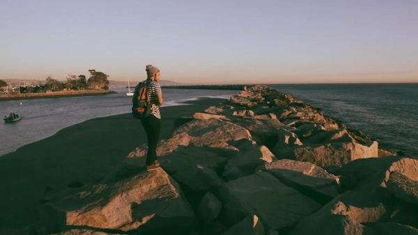 Young adult walking on jetty, takes photo Royalty-free stock video